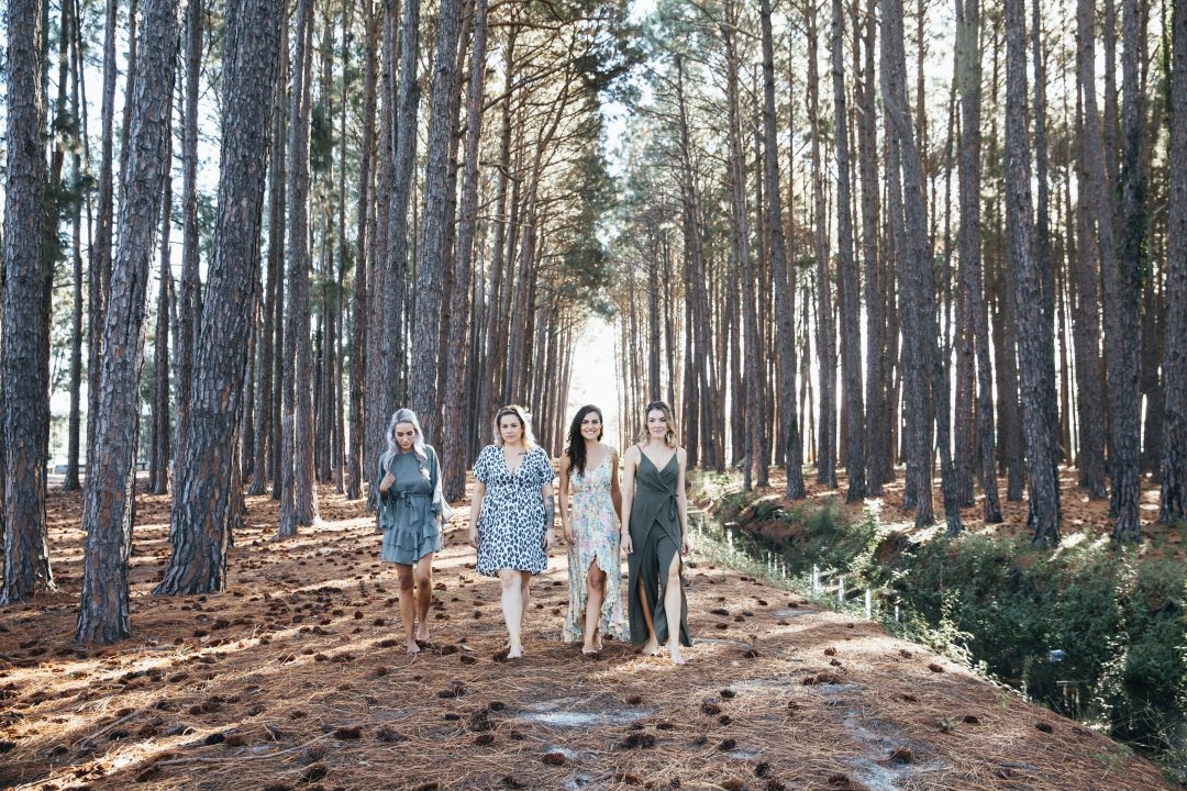 bridesmaids walking together through forest